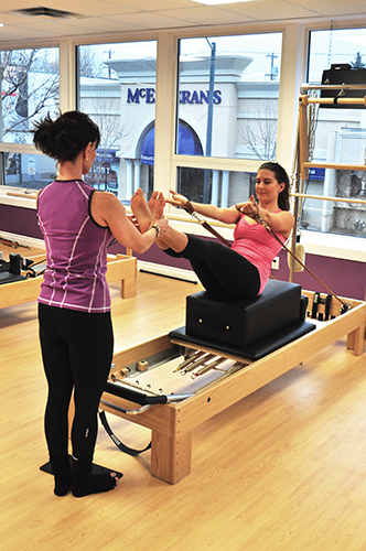 Marti Boyle with Student on the Pilates Reformer machine